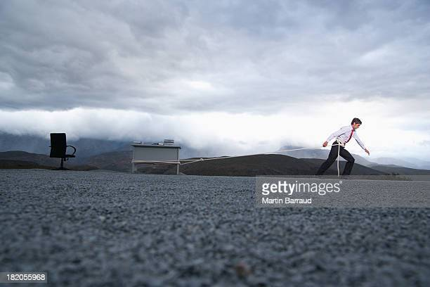 man attempting to pull his desk outdoors with a long rope - dragging stock pictures, royalty-free photos & images