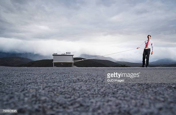 man attempting to pull his desk outdoors with a long rope - one man only stock pictures, royalty-free photos & images