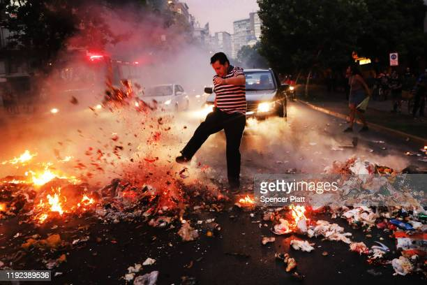 A man attempts to clear a fire set by protesters as demonstrations continue against Chilean President Sebastian Piñera the 50th consecutive day of...