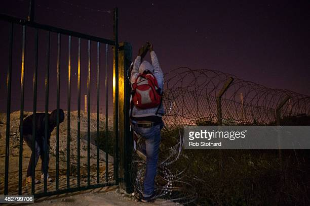 A man attempts to climb a security fence beside train tracks near the Eurotunnel terminal in Coquelles on August 3 2015 in Calais France Hundreds of...