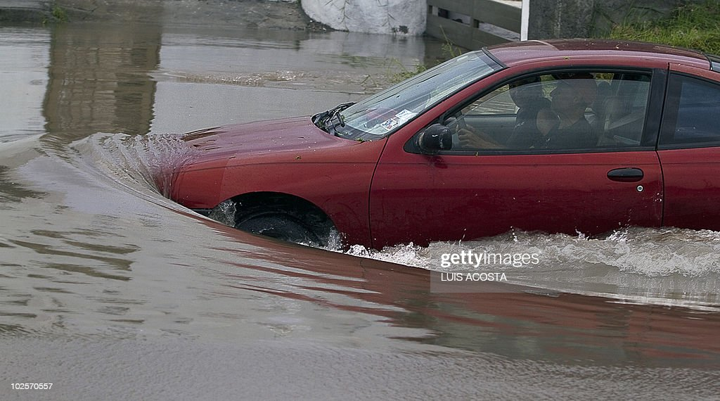 A man attempts to drive his car through a flooded street, after the passage of Hurricane Alex, in Matamoros, Tamaulipas State, on July 1, 2010. Alex, the first hurricane of the Atlantic season, weakened across northeast Mexico as it neared high mountains on Thursday, after disrupting oil clean-up operations in the Gulf of Mexico. Alex was downgraded to a tropical storm after roaring ashore late Wednesday as a Category Two hurricane slightly south of the eastern US-Mexico border. AFP PHOTO/Adrian del Angel