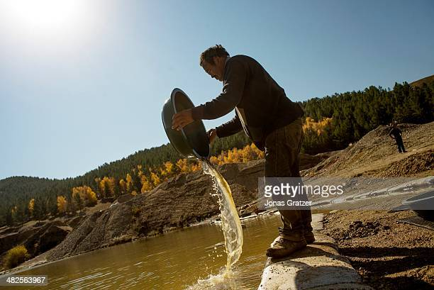 Man attempts to earn a couple grams of gold by sieving through soil and rocks mined from underground passages in the Sharygol district in Mongolia....