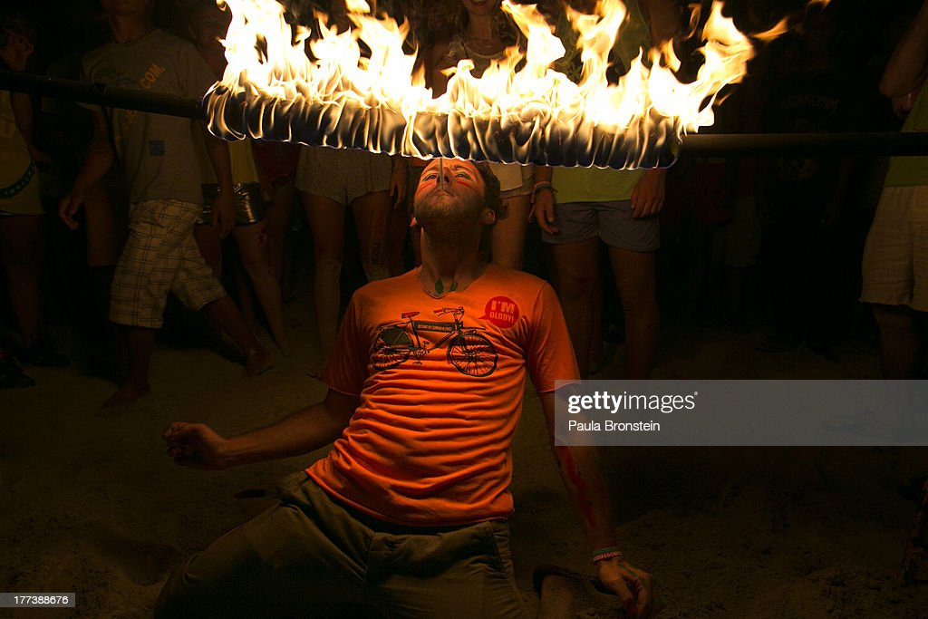 A man attempts to light a cigarette while walking underneath a burning rod during a limbo dance at the full moon party on the beach of Haad Rin on August 22, 2013 in Koh Phangan, Thailand. Thousands of people from around the world pack the Haad Rin beach enjoying the cheap liquor, drugs engaging in an all night affair. The full moon party started in late 1988 and has become one of the biggest tourist attractions for young backpackers in love with the all night beach party. It is also a huge money making venture for locals both on Koh Phangan and Koh Samui.
