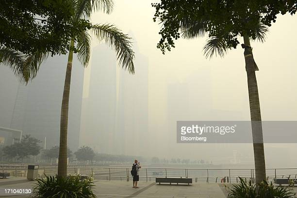 Man attempts to photograph the city skyline from the promenade at Marina Bay as buildings in the central business district stand shrouded in smog in...