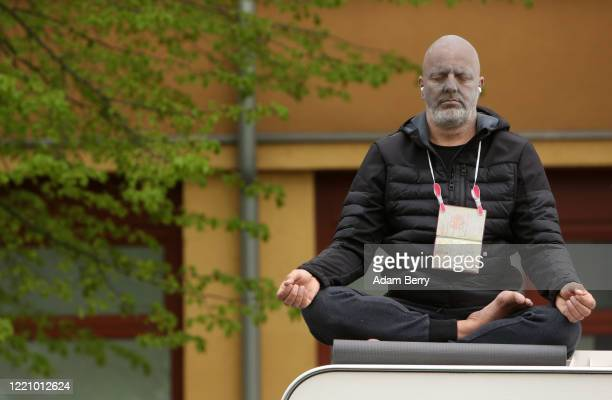 Man attempts to show he is peaceful by meditating as he demonstrates against restrictions on public life designed to stem the spread of the...