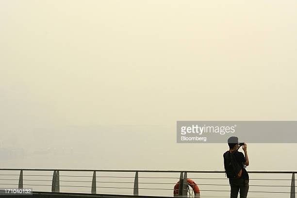 Man attempts to take a photograph of the city skyline shrouded in smog in Singapore, on Friday, June 21, 2013. Singapore's smog hit its worst level,...