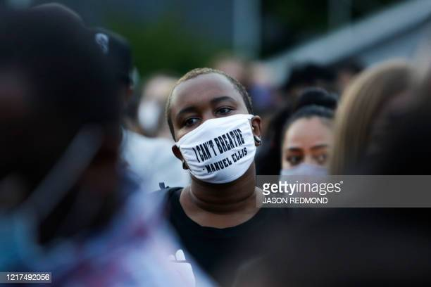 A man attending a vigil wears a mask with the words I can't breathe and the name of Manuel Ellis a 33yearold black man who died in Tacoma Police...