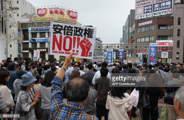"""Man attending an opposition party's election campaign rally holds up a board written """"NO, Abe administration"""" in Matsudo, Chiba prefecture October..."""
