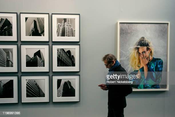 Man attending the annual Paris Photo photography art fair walks down a hallway of photographs at the Grand Palais in Paris, France on November 6,...