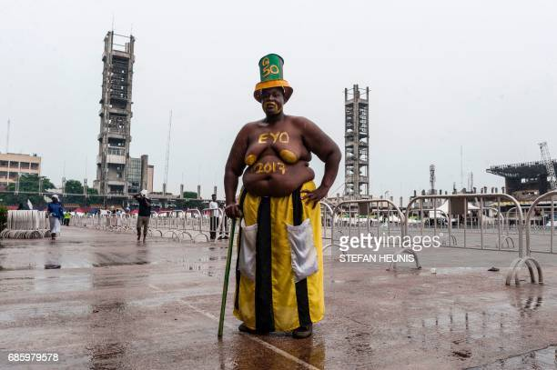 A man attending the Eyo Festival poses for a photo at Tafawa Balewa Square in Lagos on May 20 2017 The whiteclad Eyo masquerades represent the...
