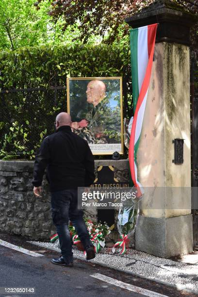 Man attends a commemoration ceremony for the death of Italian dictator Benito Mussolini and his mistress, Claretta Petacci in front of a headstone of...