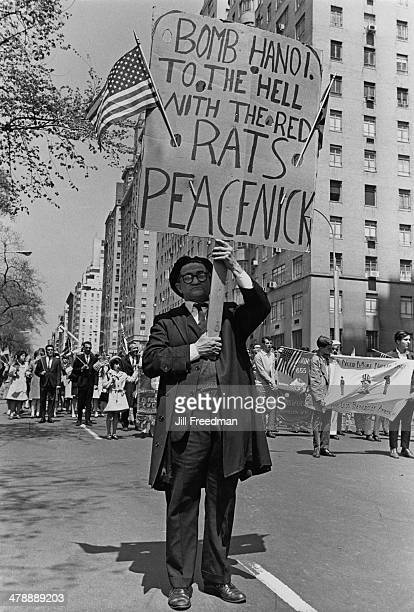 A man attends a Loyalty Day Parade in New York City holding a placard which reads 'Bomb Hanoi To the Hell with the Red Rats Peacenick' 2nd May 1967...