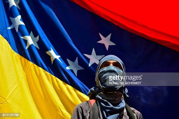 TOPSHOT A man attends a march paying homage to student Juan Pablo Pernalete killed on the eve by impact of a gas grenade during a protest against...