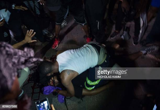 TOPSHOT A man attends to a protester who was shot during a demonstration against police brutality in Charlotte North Carolina on September 21...
