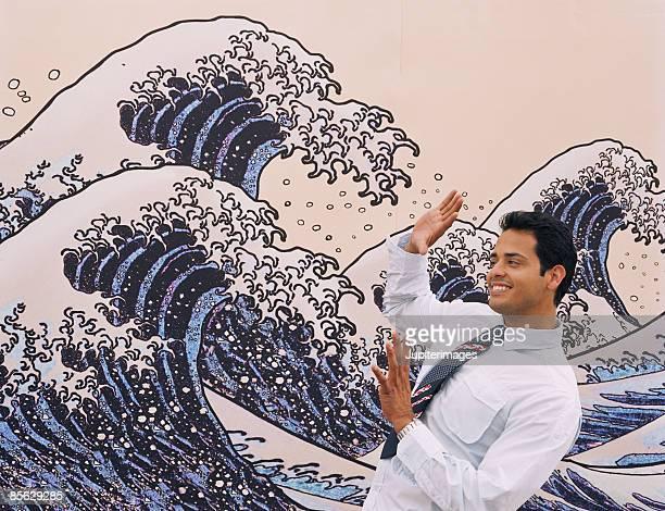 Man avoiding ocean waves on wall mural