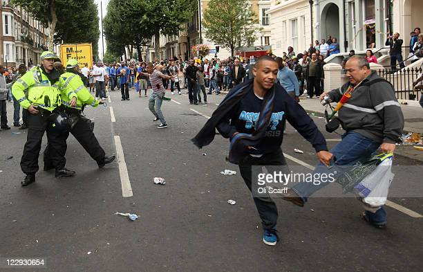 A man avoids being tripped by a member of the public as he runs down the road at the Notting Hill Carnival on August 29 2011 in London England The...