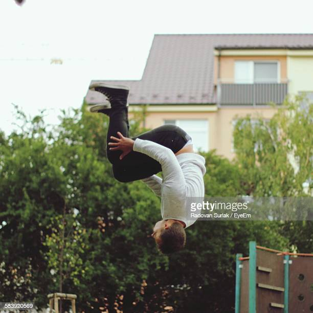 Man Backflipping In Yard Against House