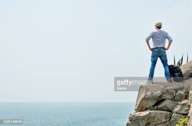 man backpacker standing on the cliff by sea - arms akimbo stock photos and pictures