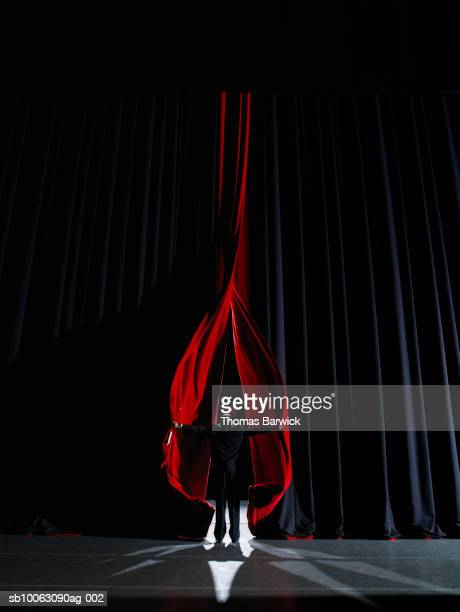 man backstage opening curtains, rear view - performing arts event stock pictures, royalty-free photos & images
