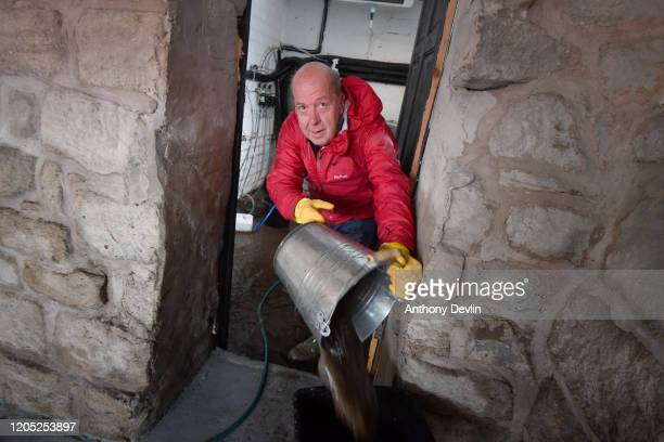A man bailsout water from Barbary's Cafe following severe flooding beside the River Calder on February 10 2020 in Mytholmroyd West Yorkshire England