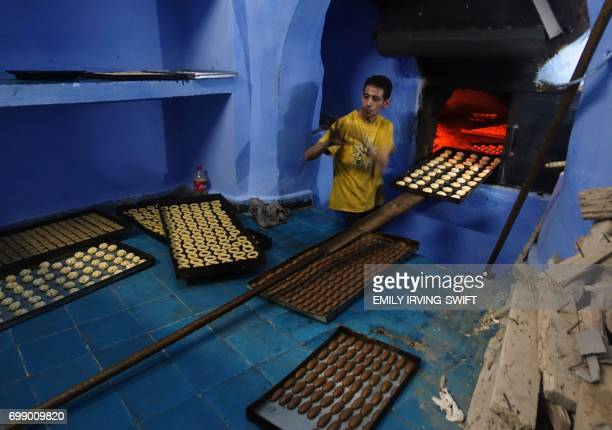 TOPSHOT A man bakes biscuits in preparation for the start of Eid marking the end of the Muslim holy fasting month of Ramadan in the northwestern...