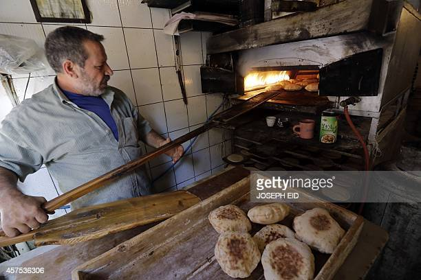 A man bakes traditional pita bread at a bakery in the coastal city of Tripoli north of Beirut on October 20 2014 AFP PHOTO/JOSEPH EID
