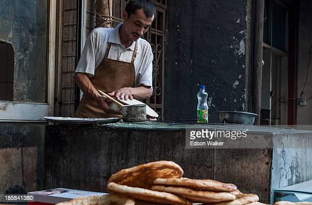 Man baking traditional bread at uygur muslim market Beiyuanmen. Xian, China, 2013.