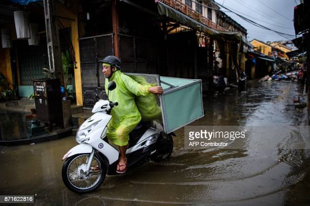 Man balances a piece of furniture as he rides his motorbike in the town of Hoi An on November 8, 2017 following days of heavy rains after Typhoon...