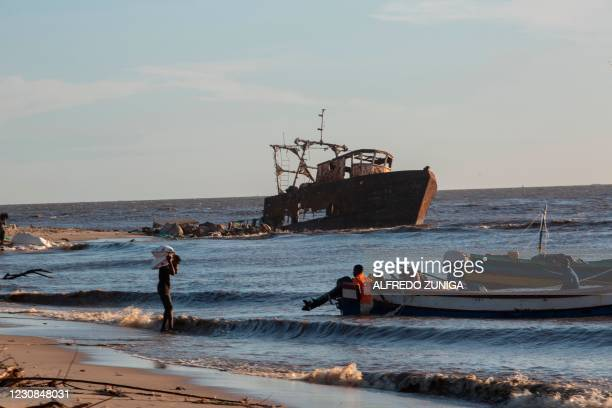 Man balances a sack on his shoulders as he walks to a boat off the beach of the Praia Nova neighborhood of the city of Beira on January 28 one of the...