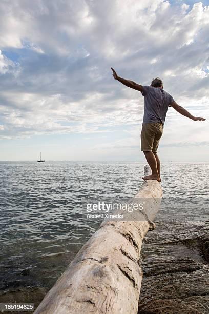 Man balances on end of log, above sea