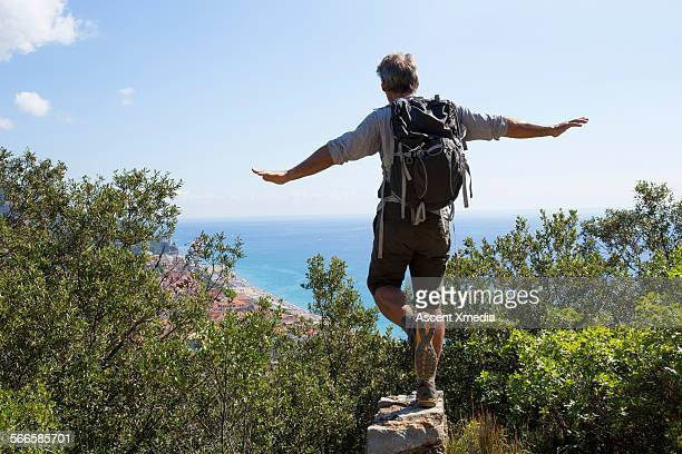 Man balances on stone wall above forest
