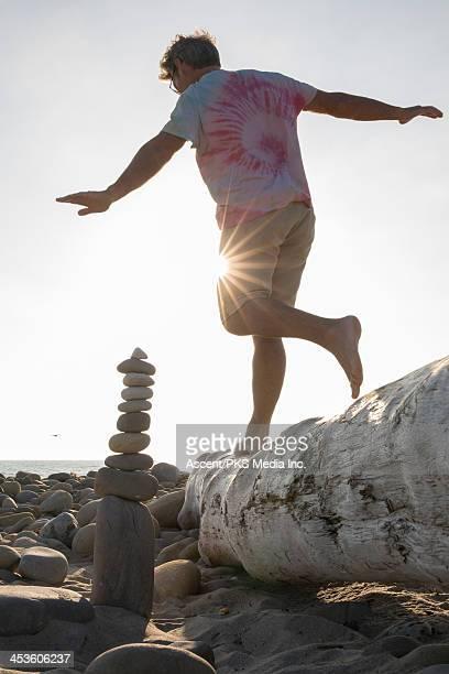 Man balances while waling on log, near zen rock pi
