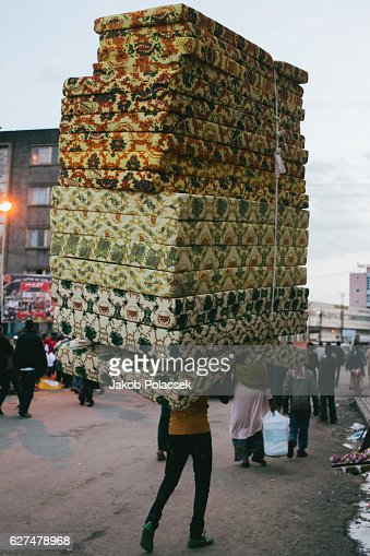 A man balancing 17 (!) mattresses on his head