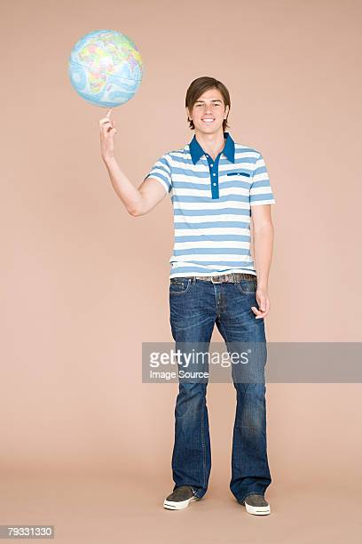 A man balancing a globe on his finger