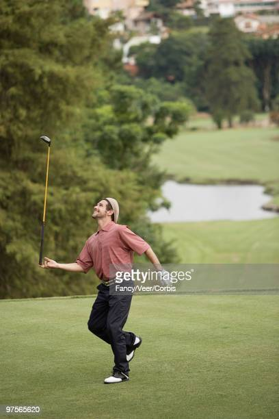 man balancing golf club on hand - golf humour photos et images de collection