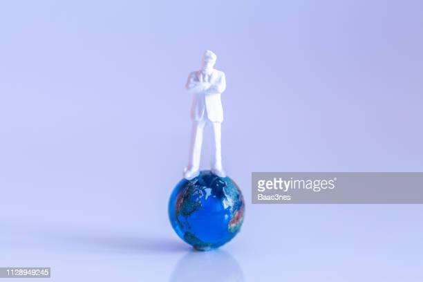 man balancing on a crystal ball - mondo beat foto e immagini stock
