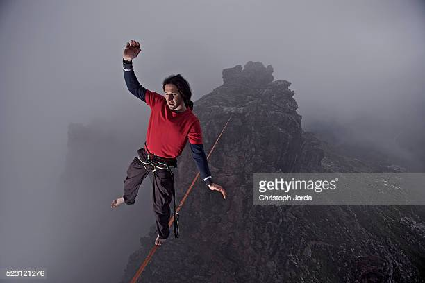 Man balancing on a high rope between two rocks
