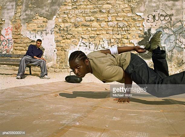 Man balancing on hand break dancing, man in background sitting on bench