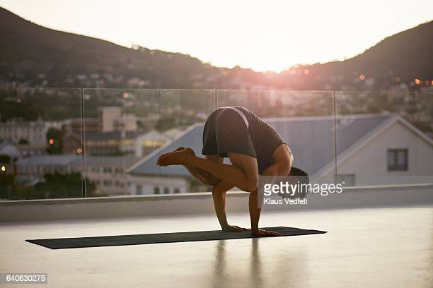 Man balancing on hands on yoga mat