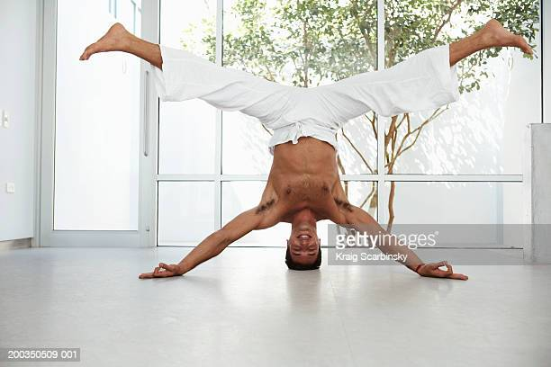 Man balancing on head, legs outstretched, portrait