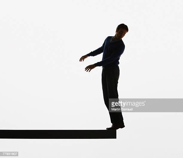 Homme en équilibre sur le bord d'une planche de bois