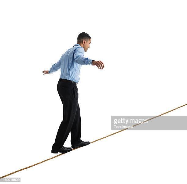 Man balancing on tightrope, studio shot