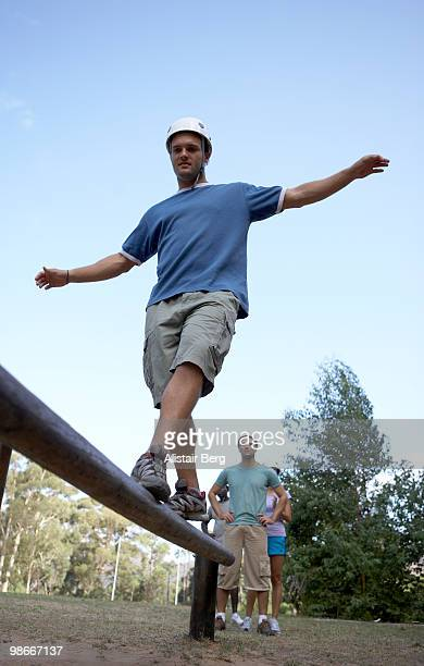 man balancing on wooden beam - balance beam stock pictures, royalty-free photos & images