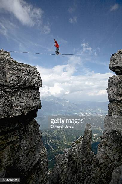 Man balancing over high rope between two cliffs in mountains, Tirol, Austria
