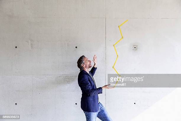 Man balancing poket rule in front of concrete wall