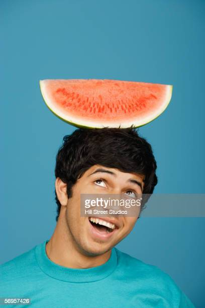 man balancing watermelon slice on head - innocence stock pictures, royalty-free photos & images