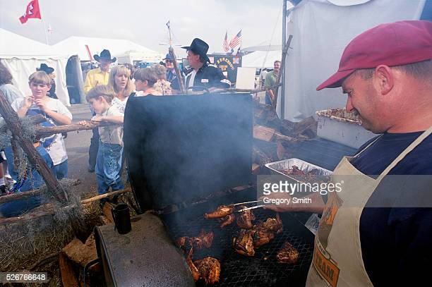A man barbecues chicken over a grill at the annual World's Championship BarBQue Contest at the Houston Livestock Show and Rodeo