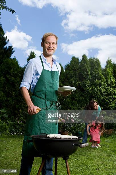 A man barbecuing bratwurst in a back yard, wife and child in the background