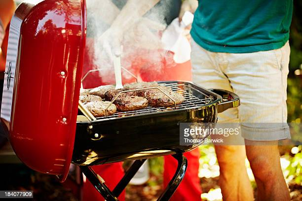 Man barbecuing burgers on grill in backyard