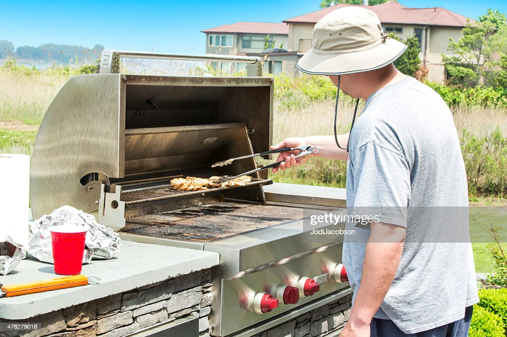 Chicken Gasgrill : Man barbecuing chicken on a outdoor gas grill stock photo getty